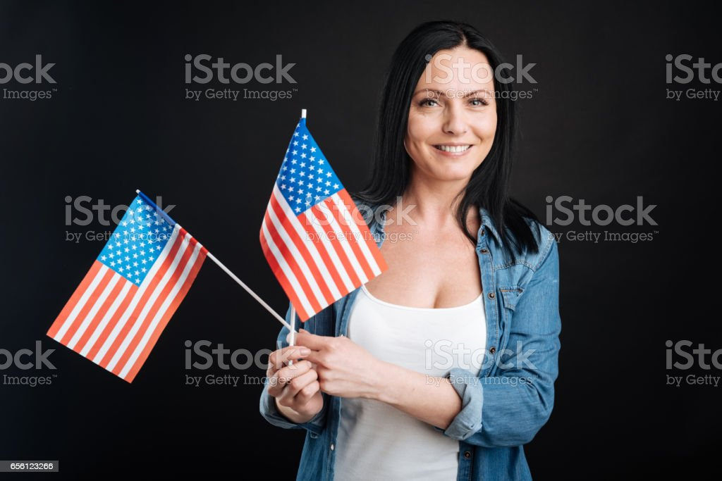 Positive delighted female keeping flags stock photo