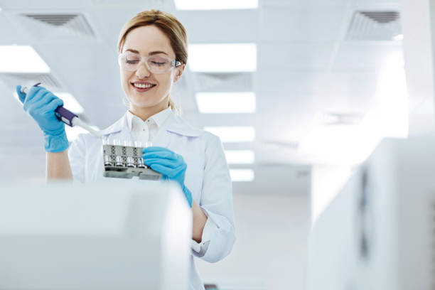 Positive delighted female scientist doing experiment Keep smiling. Attractive woman keeping medicine dropper in right hand while looking downwards and controlling the process dna purification stock pictures, royalty-free photos & images