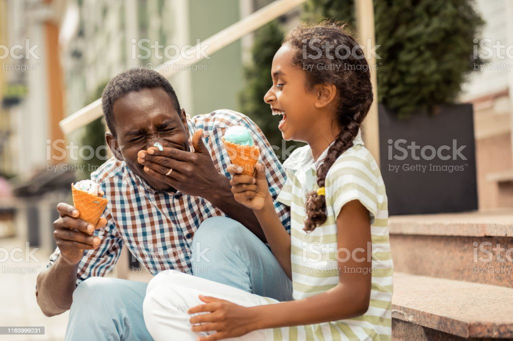 Positive delighted international male person eating ice-cream Creative father. Charming teenager laughing at funny situation, spending time with her daddy 10-11 Years Stock Photo