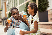Creative father. Charming teenager laughing at funny situation, spending time with her daddy