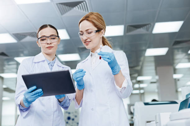 Positive delighted lab assistants looking downwards Low angle. Pretty young scientists keeping smile on faces standing in the lab while going to examine blood dna purification stock pictures, royalty-free photos & images