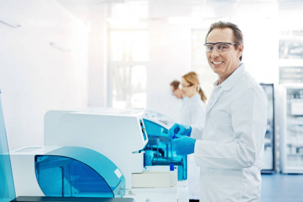 Positive delighted man in years looking straight at camera Look at me. Confident scientist keeping smile on face holding arms bent in elbows while standing in semi position dna purification stock pictures, royalty-free photos & images
