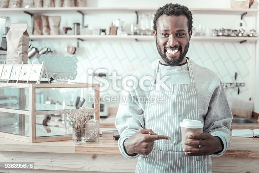 597640822istockphoto Positive delighted man pointing at the cup of coffee 936395678