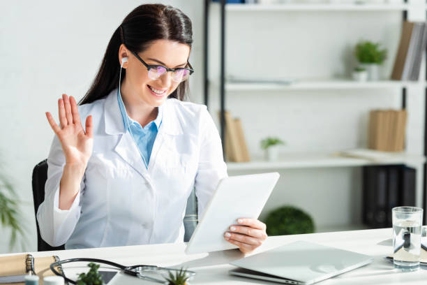 positive doctor waving and having online consultation on digital tablet in clinic office with laptop stock photo
