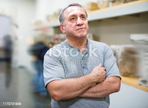Positive glad  elderly man looking with interest at ancient sculptures in museum