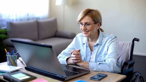 positive elderly woman in wheelchair working on laptop, it freelancer, online - remote work imagens e fotografias de stock