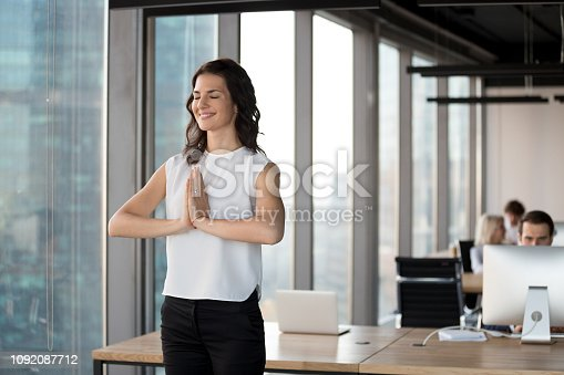 916520034istockphoto Positive employee doing yoga standing in coworking office during workday 1092087712