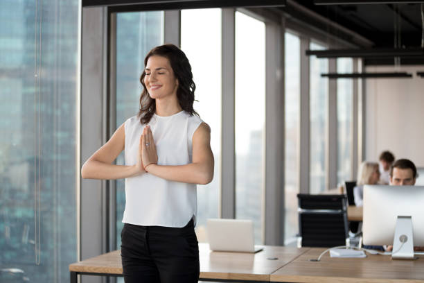 Positive employee doing yoga standing in coworking office during workday Busy employees working in contemporary office, focus on attractive employee woman with closed eyes standing in coworking holding hands in yoga greeting gesture meditating filled with positive energy yogi stock pictures, royalty-free photos & images