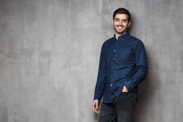Positive European Caucasian guy standing against wall in relaxed convenient pose Positive European Caucasian guy standing against wall in relaxed convenient pose only young men stock pictures, royalty-free photos & images