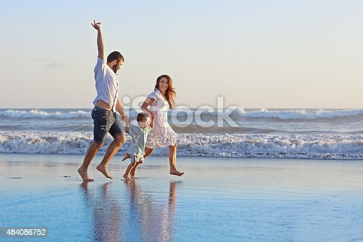 497142294 istock photo Positive family running along sea edge on the beach 484086752