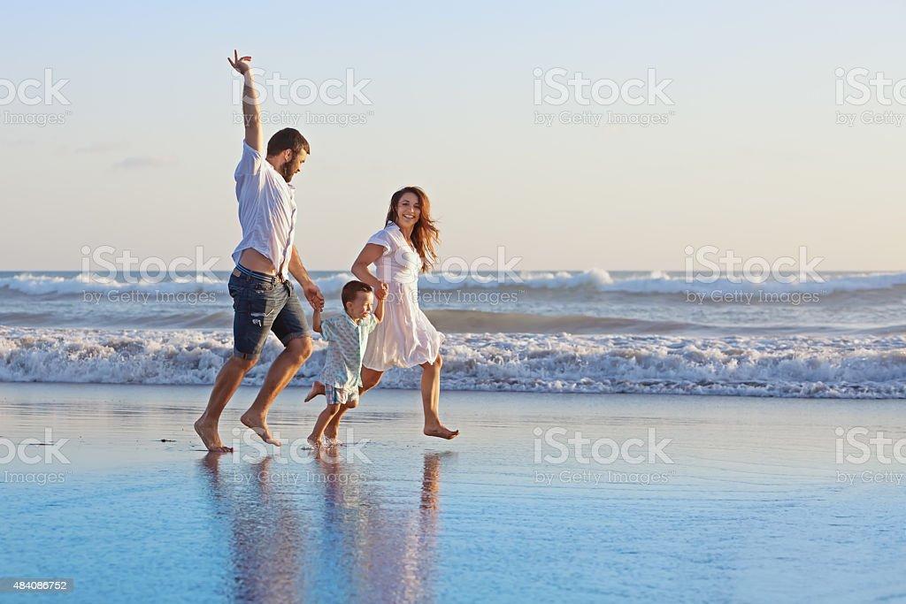 Positivas de família ao longo do Mar sobre a praia de bordo - fotografia de stock