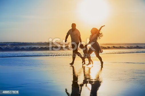 istock Positive family running with fun on the sunset beach 488527828
