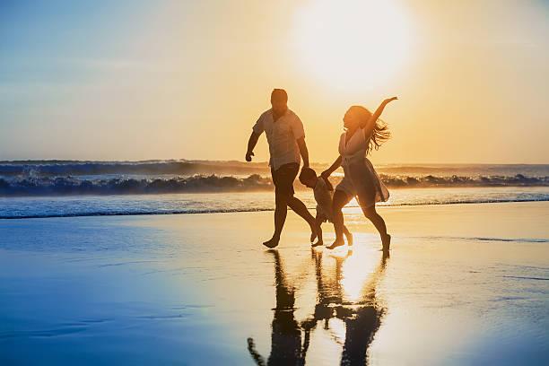 positive familie laufen spaß am strand bei sonnenuntergang - pool schritte stock-fotos und bilder