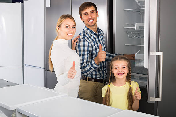 positive family selecting refrigerator - happy person buy appliances stock photos and pictures