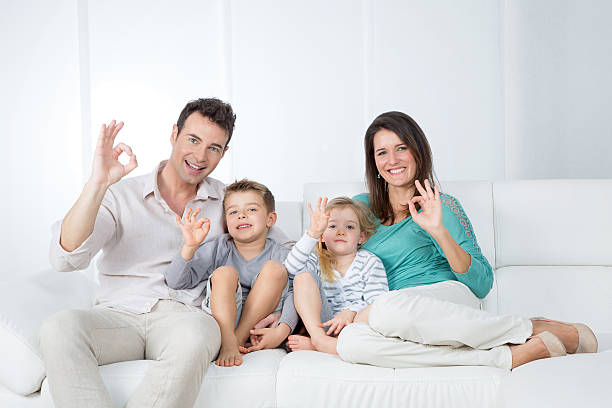 positive family sitting on sofa stock photo