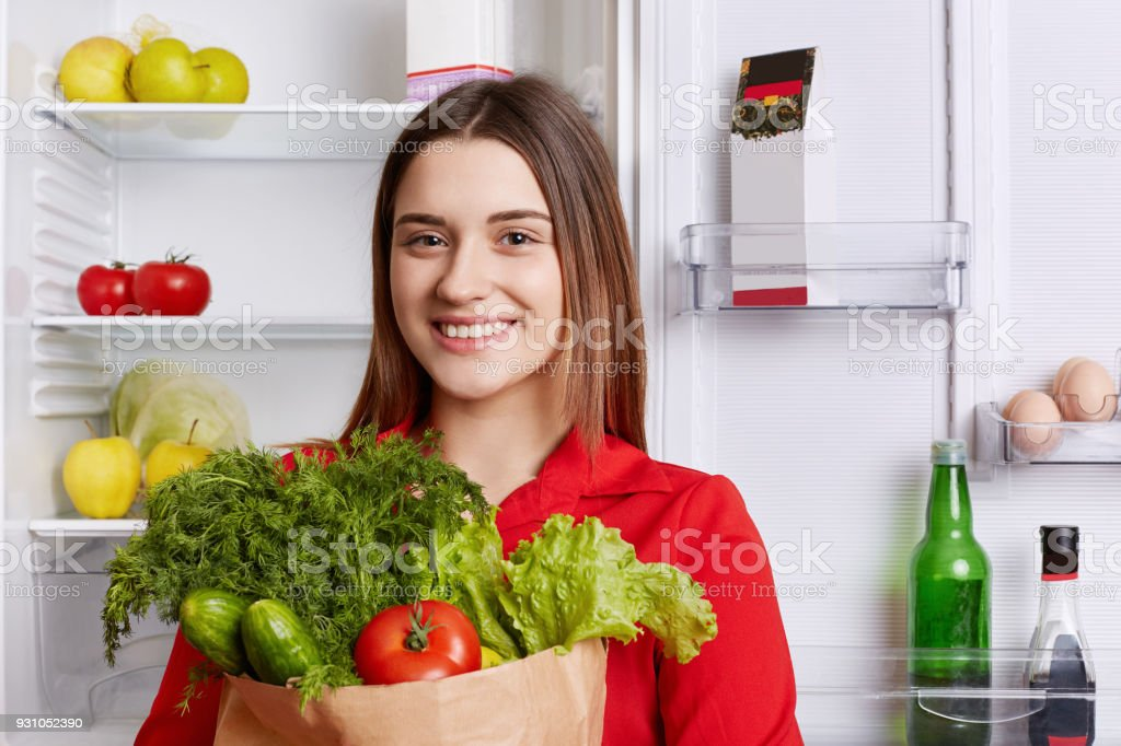 Positive female comes from grocery store with paper bag full of fresh ripe vegetables, going to put them in fridge, has happy expression. Woman vegeterian keeps to healthy diet. Eating concept stock photo