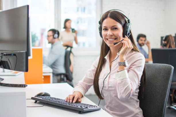 Positive female customer services agent with headset working in call center stock photo