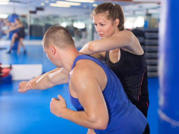 Positive female is fighting with trainer Positive female is fighting with trainer on the self-defense course for woman in sport club self defense stock pictures, royalty-free photos & images