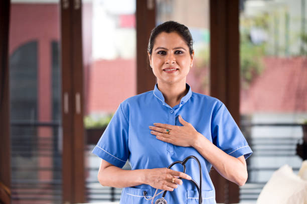 positive female nurse with hands on chest at hospital - mão no peito imagens e fotografias de stock