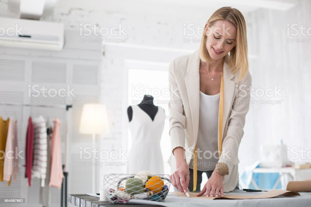 Positive female tailor drafting pattern stock photo