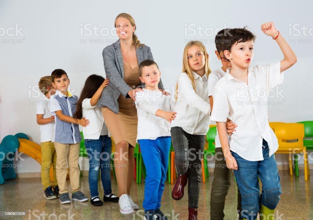 Positiva professor feminino jogo de círculo com as crianças em vejamo - foto de acervo