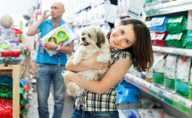 positive female with dog in pet shop, during shopping with man - pet shop and dogs not cats stock pictures, royalty-free photos & images