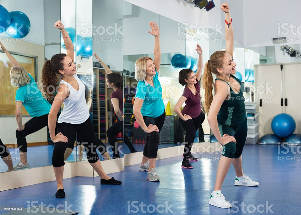 Positive females working out at aerobic class in modern gym royalty-free stock photo