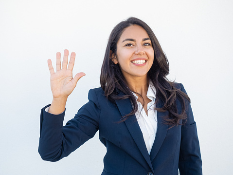 Positive friendly businesswoman making greeting gesture. Front view of smiling beautiful young Latin woman in office suit waving hand and saying hello. Gesturing concept