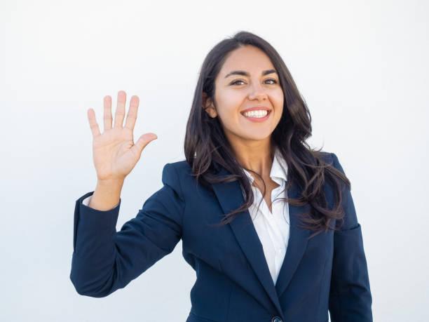 positive friendly businesswoman making greeting gesture - sventolare la mano foto e immagini stock