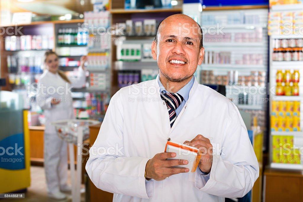 Positive friendly pharmacist and pharmacy technician stock photo