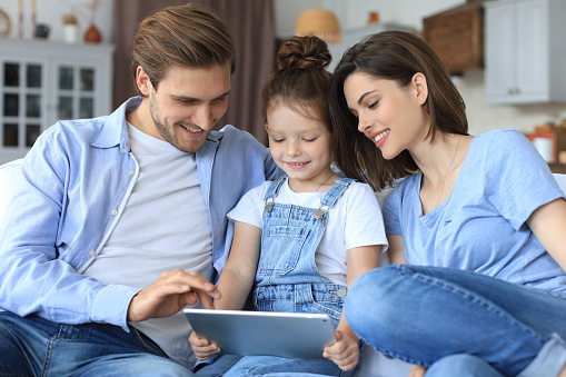 871175856 istock photo Positive friendly young parents with smiling little daughter sitting on sofa together answering video call on digital tablet while relaxing at home on weekend. 1267502182