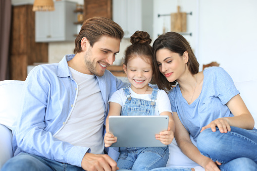 871175856 istock photo Positive friendly young parents with smiling little daughter sitting on sofa together answering video call on digital tablet while relaxing at home on weekend. 1267503600