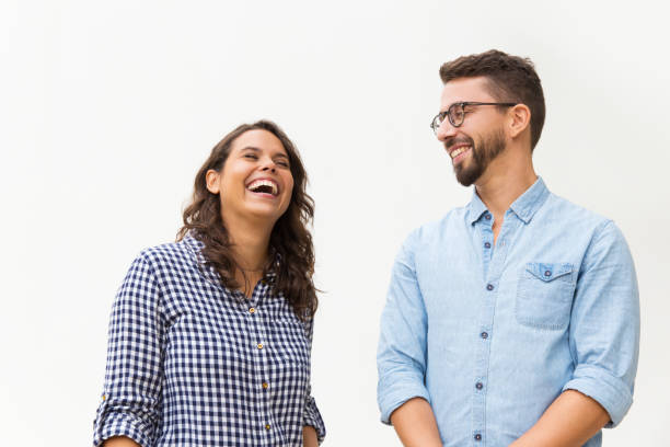 Positive funny guy making his girlfriend laugh stock photo