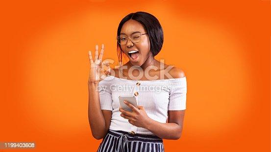 istock Positive Girl Holding Phone Gesturing Okay And Winking, Orange Background 1199403608