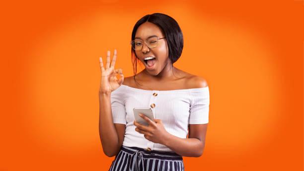 Positive Girl Holding Phone Gesturing Okay And Winking, Orange Background stock photo