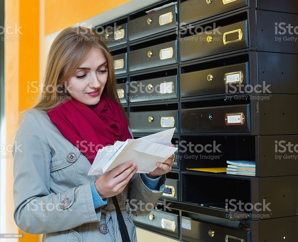 Positive girl in outwear receiving correspondence stock photo