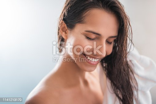 istock Positive girl keeping hair with towel 1141213170