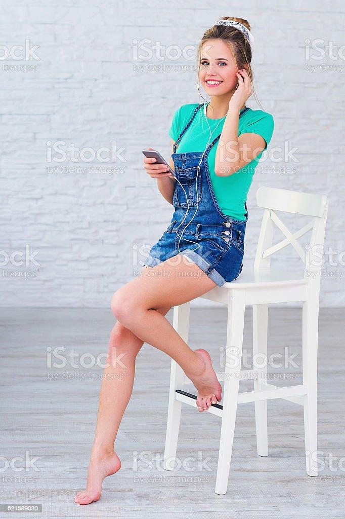 Positive girl listening to music in earphones stock photo