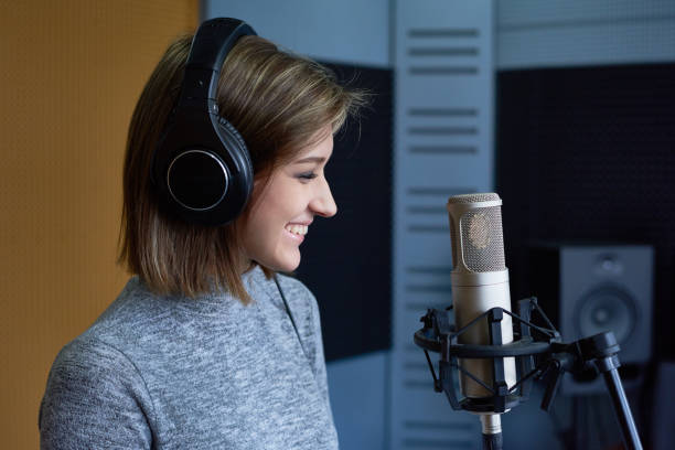 Positive girl recording song Excited female radio host broadcasting through microphone in studio radio dj stock pictures, royalty-free photos & images