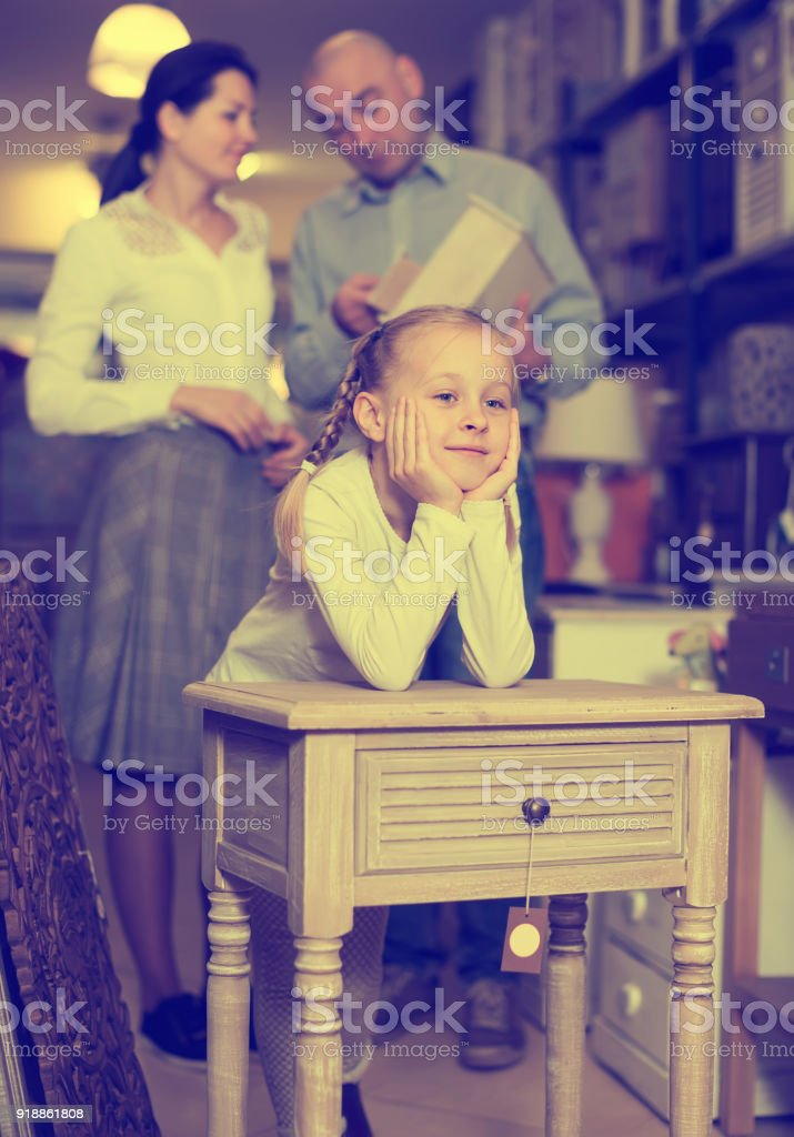 Positive girl stading with curbstone in furniture shop stock photo