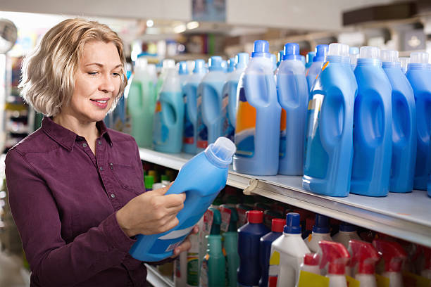 Positive glad female with selecting fabric conditioner Positive glad female with selecting fabric conditioner in household store laundry detergent stock pictures, royalty-free photos & images