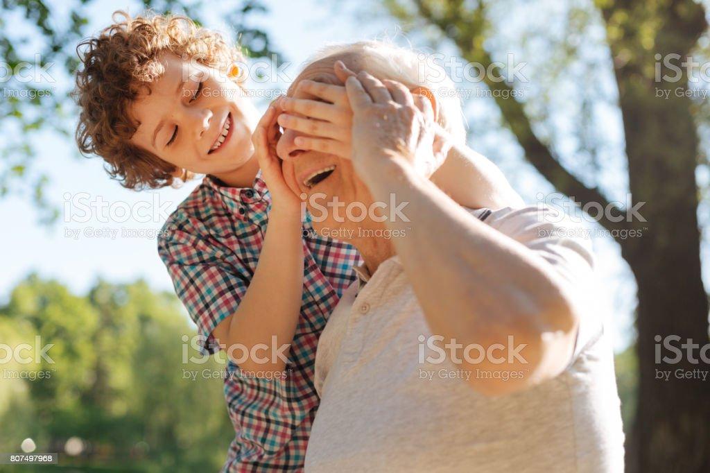 Nieto positivo que cubre los ojos de su pariente - foto de stock