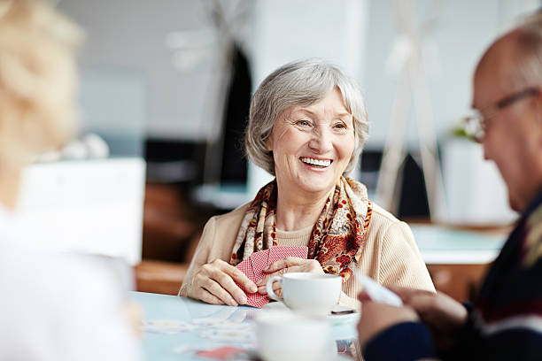 Positive granny with her friends Senior people playing cards in cafe playing card stock pictures, royalty-free photos & images