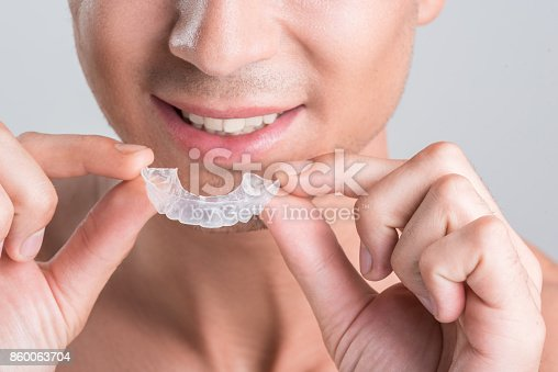 istock Positive guy is demonstrating transparent brace for teeth 860063704