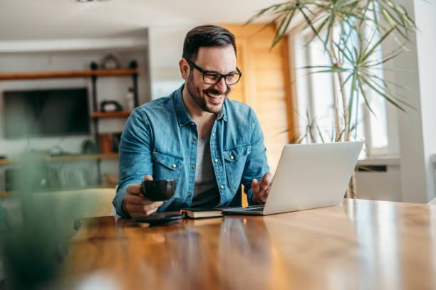 Un hombre guapo positivo mirando la computadora portátil, sosteniendo una taza de café, retrato. - foto de stock