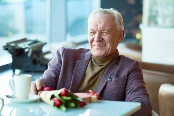 Positive handsome senior man enjoying romantic date stock photo