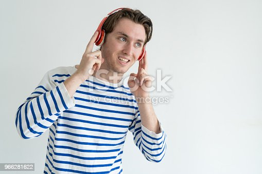 Positive handsome young man in headphones listening to music and looking away. Jolly guy in casual sweater enjoying audio book. Leisure concept