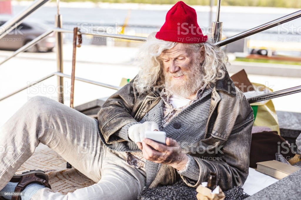 Positive homeless man enjoying new technology zbiór zdjęć royalty-free