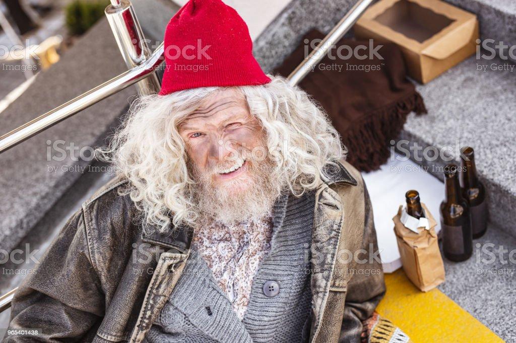 Positive homeless man sitting on the stairs zbiór zdjęć royalty-free