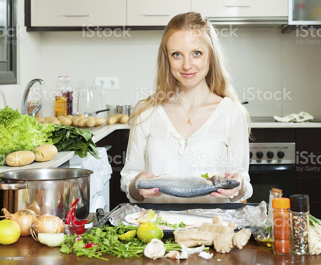 Positive housewife cooking full fish with lemon stock photo